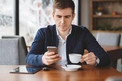 il-giovane-uomo-d-affari-legge-sms-sul-telefono-caffe-67195082